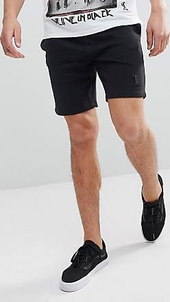 34f2113928b48 Religion Pantalones cortos negros de punto con emblema de metal de Religion