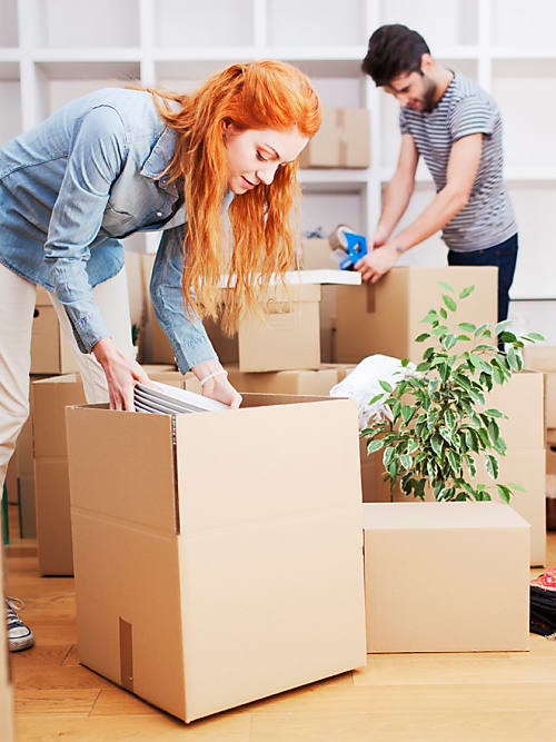 A man and a woman unpacking boxes in their new home.